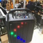 Портативная акустическая система с аккумулятором, светодиодной подсветкой, колёсами и ручкой.